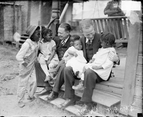 [Actors Charles J. Correll and Freeman F. Gosden from the Amos 'n Andy show, holding two African American children on their knees, sitting on the steps in front of a building]