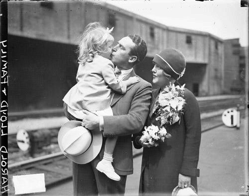 [Actor Harold Lloyd standing with his wife, holding and kissing his young daughter on a railroad platform]