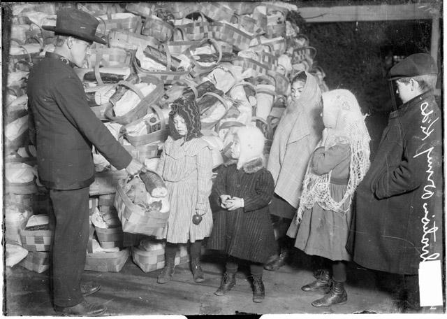 [Salvation Army officer giving a Christmas basket to a child]