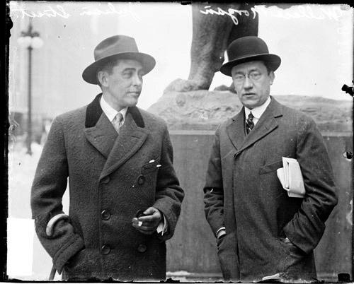 [Julian Street and Wallace Morgan standing on South Michigan Avenue at the base of a statue of a lion in front of the Art Institute]