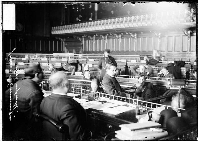 [Edward Cummings, stage carpenter, testifying before the speaker's rostrum in the council chamber during the Iroquois Theater fire investigation]