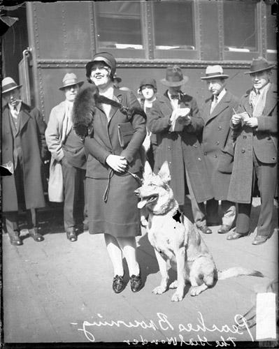 [Actress Frances Heenan Browning (known as Peaches or The Girl Wonder) looking towards camera and smiling, standing with a German Shepherd dog]