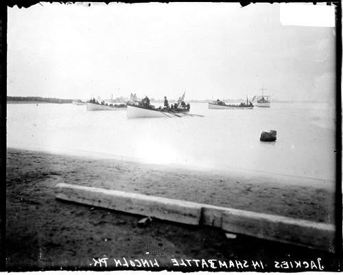 [Boats full of Naval apprentices on Lake Michigan landing in Lincoln Park during mock battle, three row boats and a patrol boat visible]