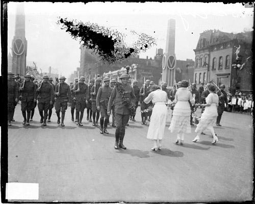 [13th Engineers Division, soldiers marching between victory obelisks on street in Loop community]