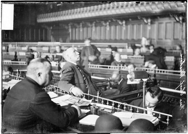[Fire chief William Musham testifying before the speaker's rostrum of the council chamber during the Iroquois Theater fire investigation]