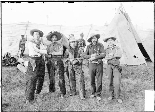 [Five men in frontier dress posed standing next to each other in a fenced area with teepee and other people in the background at the Madison Street Carnival]