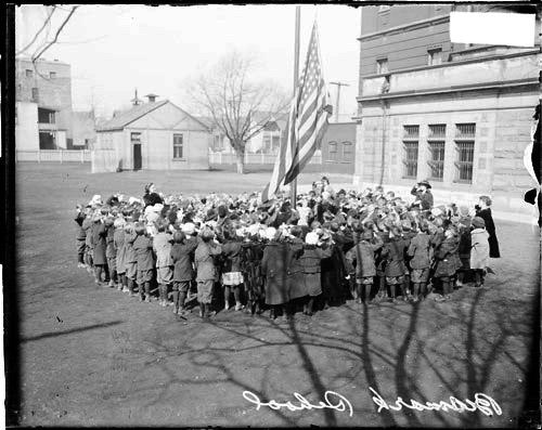 [School children saluting American flag being raised up a pole, on the grounds of Bismarck School at 2010 North Central Park Avenue]