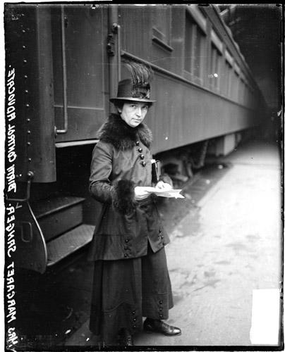 [Birth control advocate, Margaret Sanger, standing next to a train in a station]
