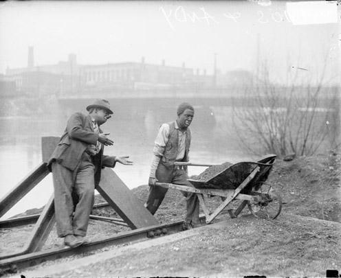[Actors Charles J. Correll and Freeman F. Gosden from the Amos 'n Andy show, wearing blackface, standing near the shore of a body of water while pushing a wheelbarrow]