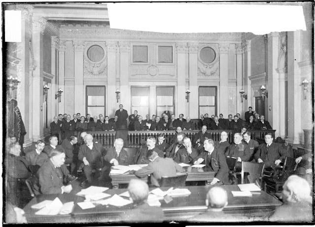 [Interstate Commerce Commission men sitting around a table in a room between the seating area and the bench]