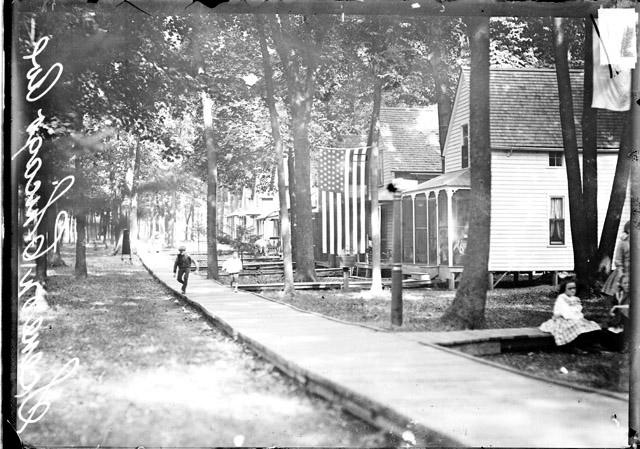 [Boys running on boardwalk in front of cottages at the Des Plaines Methodist Camp Ground]