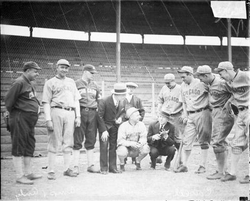 [Actors Charlie J. Correll and Freeman Gosden of the WMAQ radio program Amos 'n Andy, posing with eight members of a Chicago baseball team on a field at a baseball stadium]