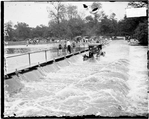 [Automobile moving through water next to a sloping wall alongside the Des Plaines River]