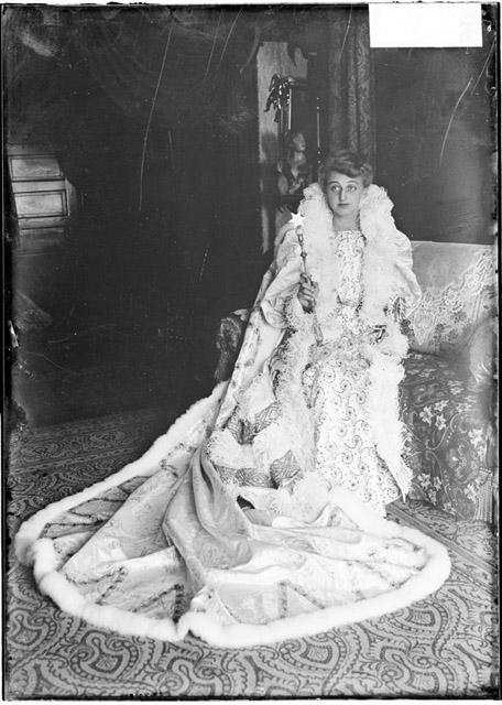 [Lucille Nau, dressed for the 1904 Madison Street Merchants Carnival in a gown and cape and holding a scepter, sitting on a couch]