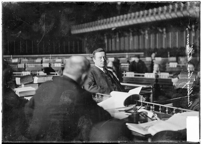 [City building inspector George Williams, looking ahead, testifying before the speaker's rostrum in the council chamber during the Iroquois Theater fire investigation]