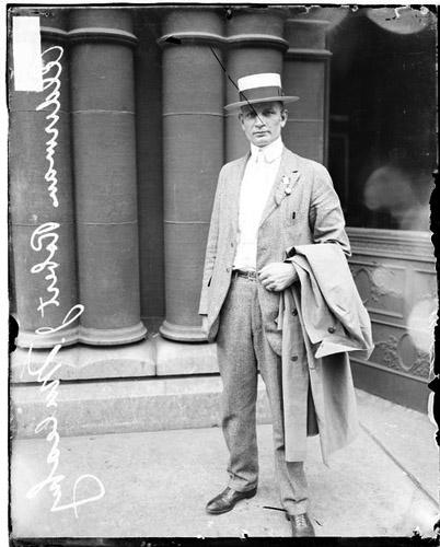 [5th ward alderman, Robert J. Mulcahy, standing on a sidewalk]