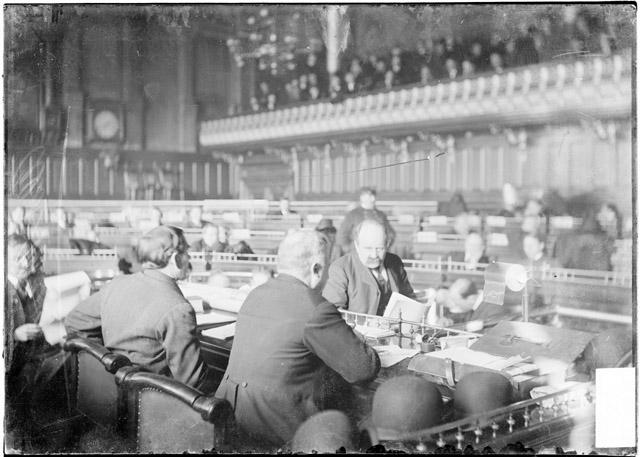 [Alderman William testifying before the speaker's desk of the Council Chamber during the Iroquois Theater fire investigation]