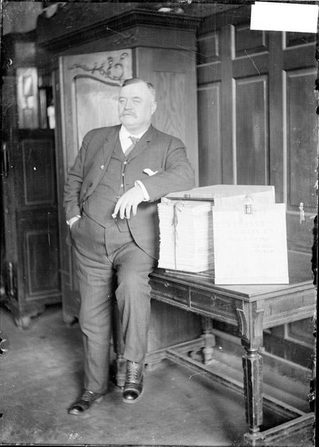 [Deputy Coroner Buckley leaning against a table with a box of papers labeled: Testimony and verdicts of the Iroquois Theater fire case and verdicts, Dec. 1903, Jan 1904]