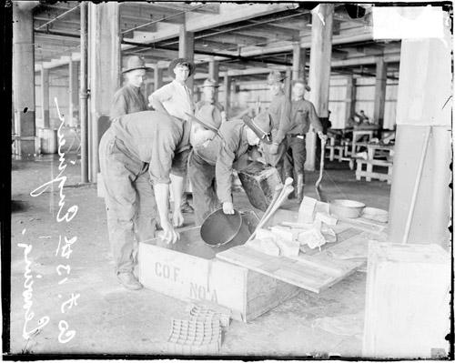 [13th Army Engineers packing mess gear into a crate as they are preparing to leave for Camp Logan]