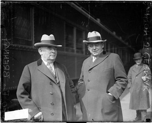 [Anton J. Cermak, President of the Cook County Board of Commissioners, and George E. Brennan, Democratic leader in Chicago, standing next to a train, Brennan looking toward the camera]