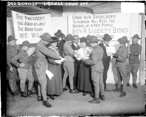 [Boy Scouts wearing U.S. Army uniforms selling Liberty Bonds to several men and women in a room]