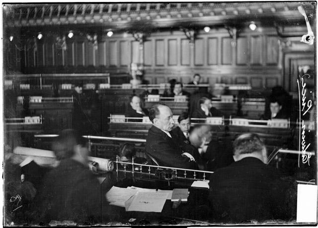 [Edwin Price, with his arms crossed in front of his chest, testifying before the speaker's rostrum in the council chamber during the Iroquois Theater fire investigation]