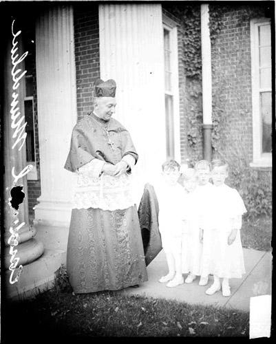 [Cardinal Mundelein standing with four young boys in front of a building]
