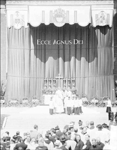 [International Eucharistic Congress in Mundelein, Illinois, with altar boys standing around a group of clergymen on an altar]