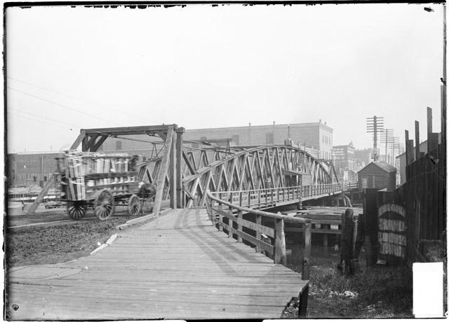 [Old Archer Avenue swing bridge, looking along the exterior length of the bridge over the Chicago River and showing a horse drawn cart is going over the bridge]