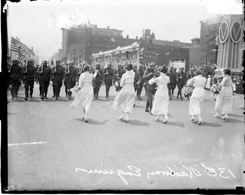 [13th Engineers Division, four women greeting soldiers marching along street in Loop community]
