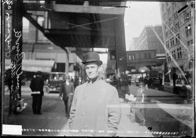 [State's Attorney Edmund Burke of Sangamon City standing underneath a portion of the elevated train tracks in the Loop]