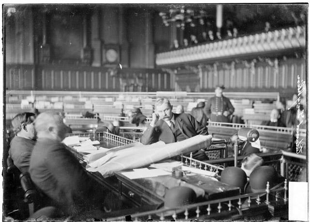 [Edward Laughlin sitting before the speaker's rostrum, which is covered with large papers, in the council chamber during the Iroquois Theater fire investigation]