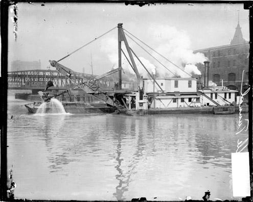 [Barge with a crane digging in the Chicago River, constructing the LaSalle Street Tunnel]