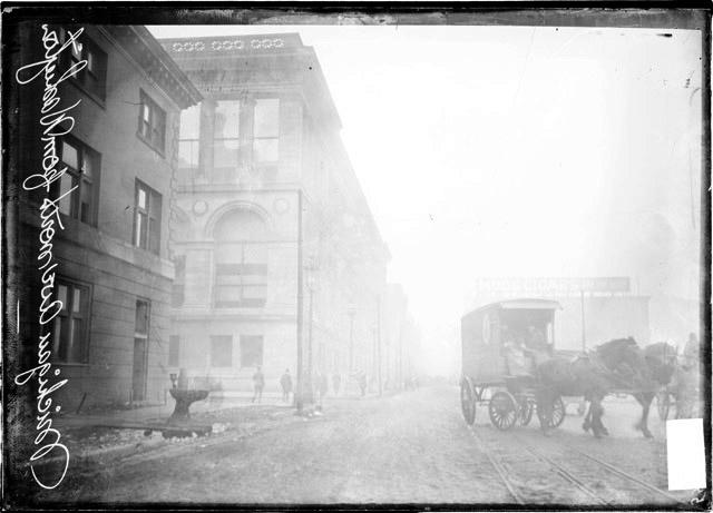 [Michigan Avenue, looking north, showing the main Chicago Public Library on one side of the street and a horse drawn van driving along Michigan Avenue]