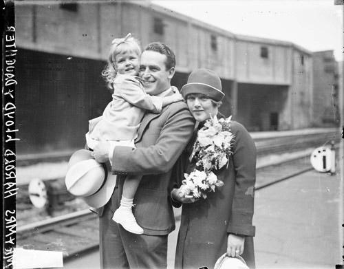 [Actor Harold Lloyd looking to the left of the camera, standing with his wife, holding his young daughter on a railroad platform]
