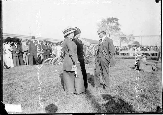 [Mrs. Glen Curtis, Mrs. Blanche S. Scott, and Charles F. Willard standing in a field]