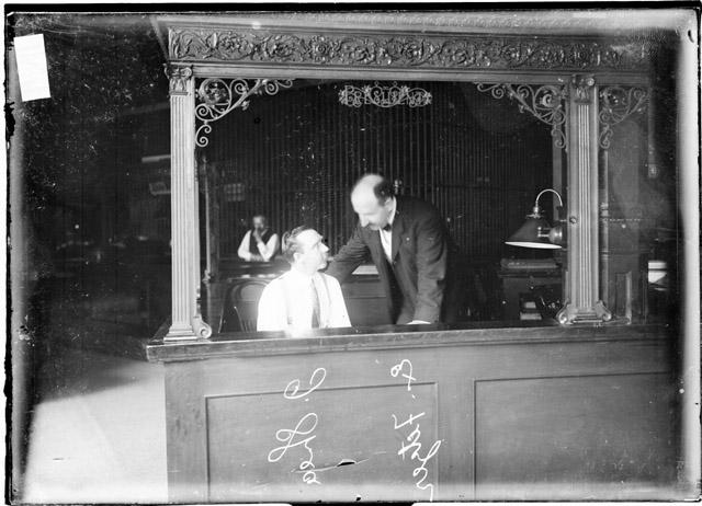 [Bank employees J. Shea and Ex. Fetzer speaking to each other behind a desk inside the Milwaukee Avenue State Bank during a bank failure]