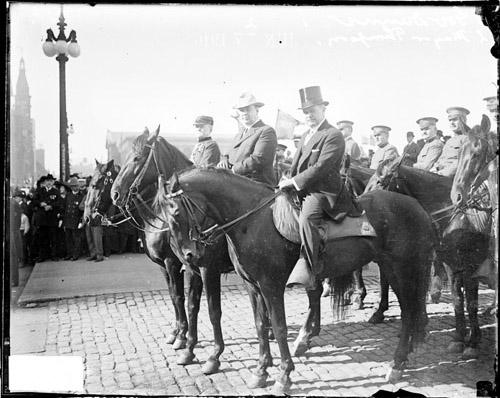 [Mayor, William Hale Thompson, and Governor Dunne, on horseback on a cobblestone street during a parade]
