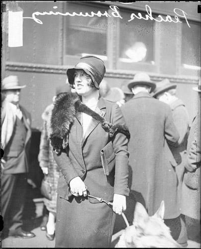[Actress Frances Heenan Browning (known as Peaches or The Girl Wonder) looking to her right, standing with a German Shepherd dog by a train car]