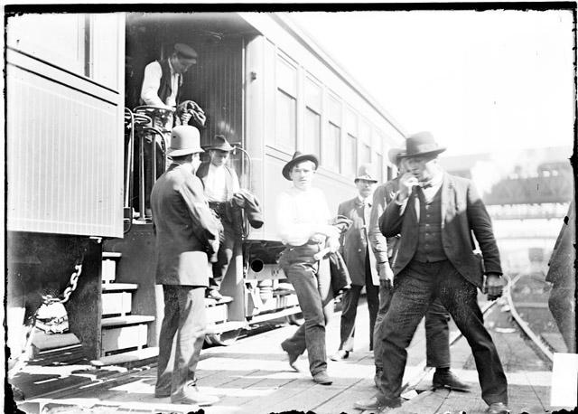 [Men disembarking from a train while a policeman watches during the 1904 Stockyards Strike]