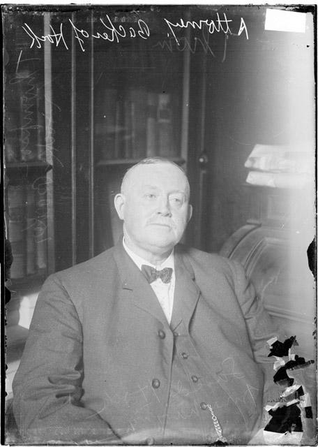 [Albert H. Thompson, attorney in Johann Hoch case, leaning back in his chair, sitting next to a desk, light exposure]