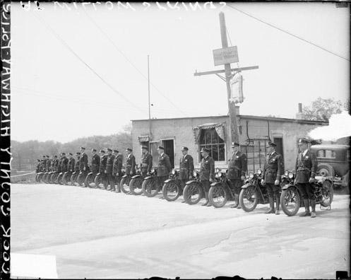 [Group of Cook County highway police officer standing next to motorcycles in front of a building]