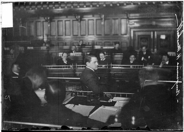 [Benjamin H. Marshall, seen in profile, testifying before the speaker's rostrum in the council chamber during the Iroquois Theater fire investigation]