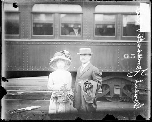 [Consul S. Yamasaki and his wife standing on a railroad platform in front of a passenger car]