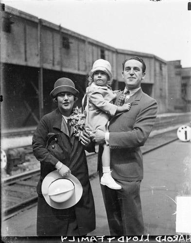 [Actor Harold Lloyd standing with his wife, holding his young daughter on a railroad platform]