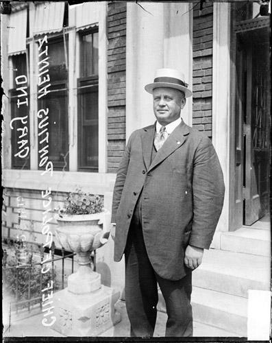 [Chief of Police of Gary, Indiana, Pontius Heintz, standing in front of a brick building]