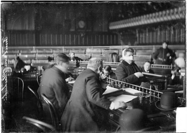 [Emil von Planchecki, with bandages on his hand and face, testifying before the speaker's rostrum in the council chamber during the Iroquois Theater fire investigation]