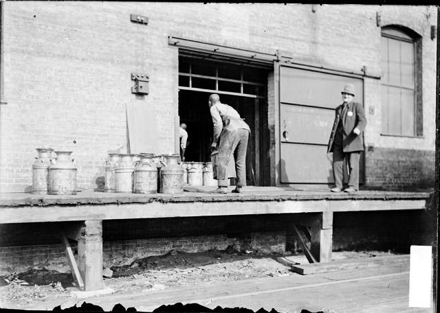 [African American man lifting a metal container while a policeman stands by during the 1904 Stockyards Strike]