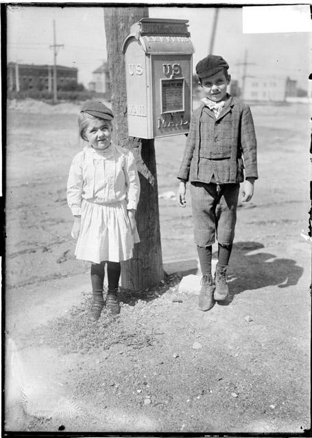 [Richard Naddy and his sister standing on a sidewalk next to a mailbox]
