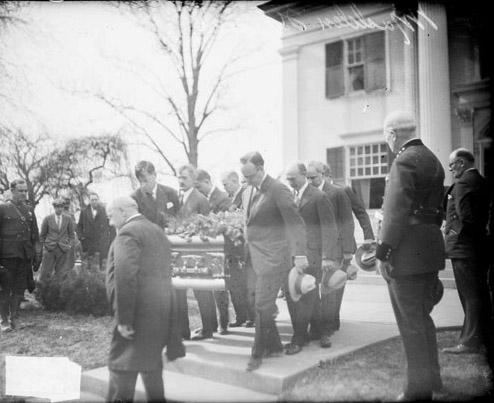 [Eight men carrying the casket of Martin B. Madden down steps in front of a large building]